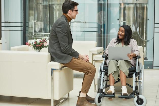 彼女が車椅子に座って、オフィスでラップトップに取り組んでいる間、彼の同僚と話しているビジネスマン