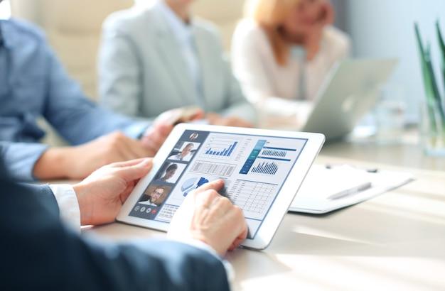 Бизнесмен разговаривает со своими коллегами по видеоконференции. деловая команда, работающая из офиса с помощью цифрового планшета, обсуждает финансовый отчет своей компании