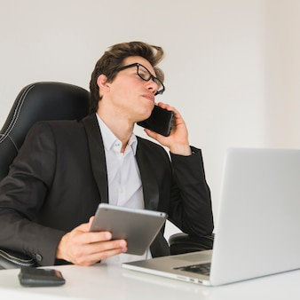 Businessman talking with cellphone while using digital tablet
