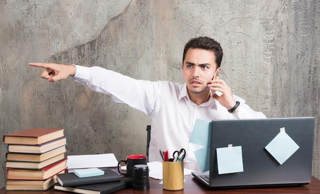 Бизнесмен разговаривает с телефоном и указывая его стороной на офисный стол.