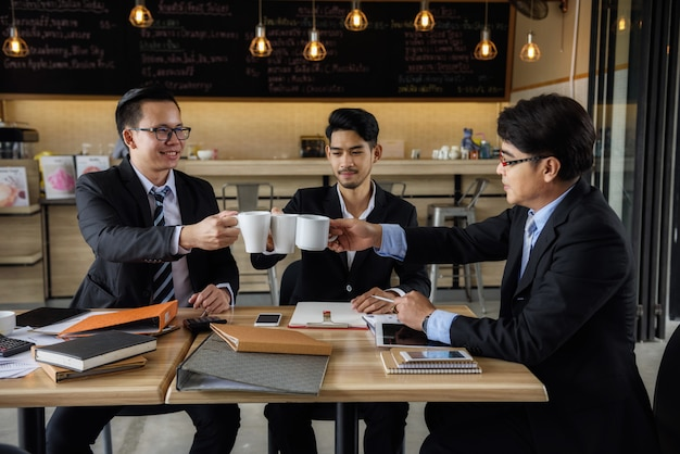 Businessman team clink hot coffee in cafe