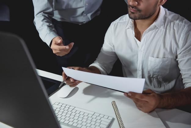 Бизнесмен команда обсуждает проект в офисе ночью