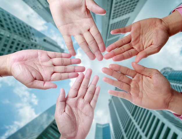 Businessman teamwork with hand together in middle of office buidling.