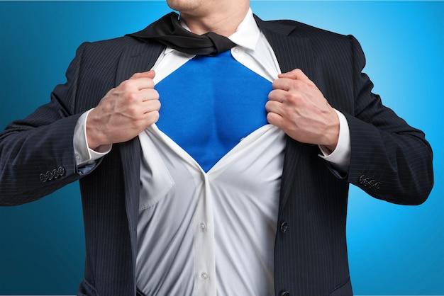 Бизнесмен разрывает рубашку на себе, чтобы показать, что он супермен, изолированный на фоне
