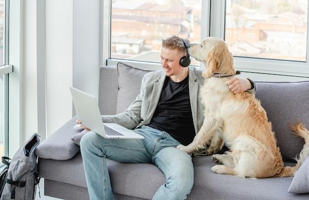 Бизнесмен телеработы рядом с собакой