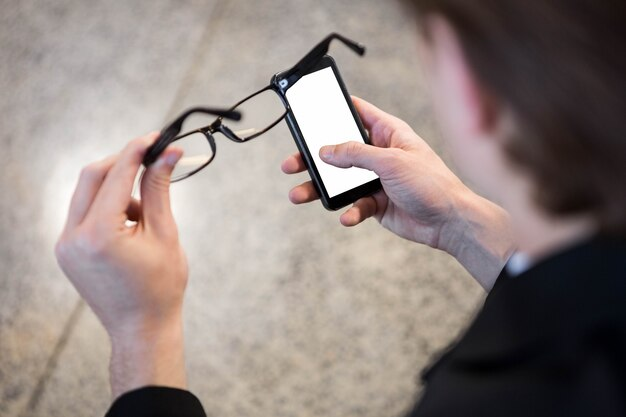 Businessman text messaging on mobile phone in office