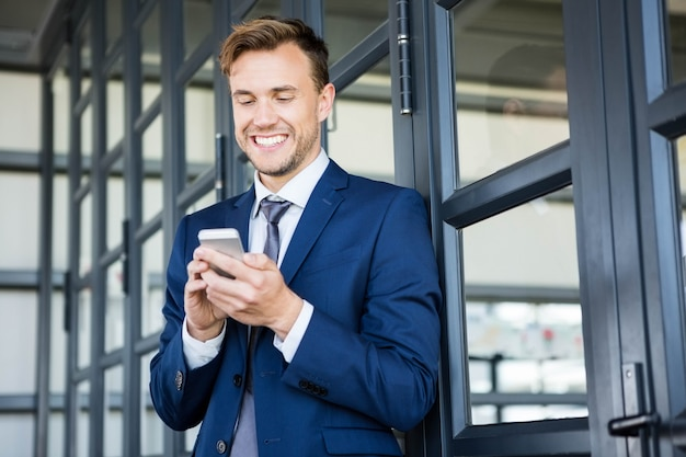 Businessman text messaging on smartphone in office