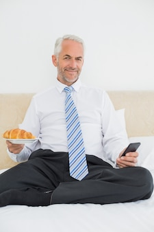 Businessman text messaging while holding croissant in bed