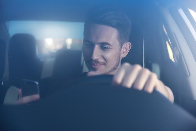Бизнесмен текстовых сообщений на своем мобильном телефоне во время вождения. опасный водитель.