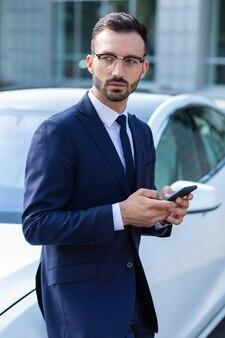 Бизнесмен текстовых сообщений жене. бородатый бизнесмен в очках пишет текстовые сообщения жене, ожидая ее возле машины