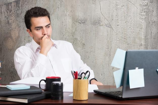 사무실 책상에서 회사에 대해 생각하는 사업가.
