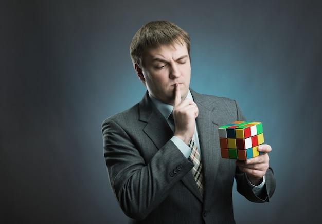 Businessman thinking how to solve rubik cube