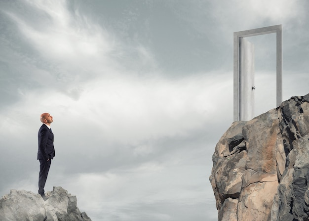 Businessman thinks about how to get to a door. concept of ambition in business