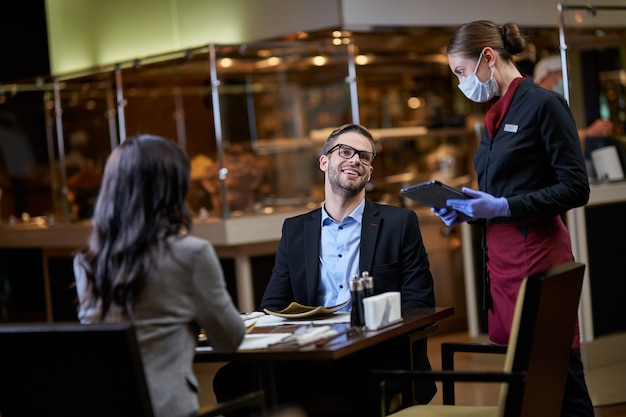 Businessman throwing his head back with a smile and talking to a female server about his order in a restaurant
