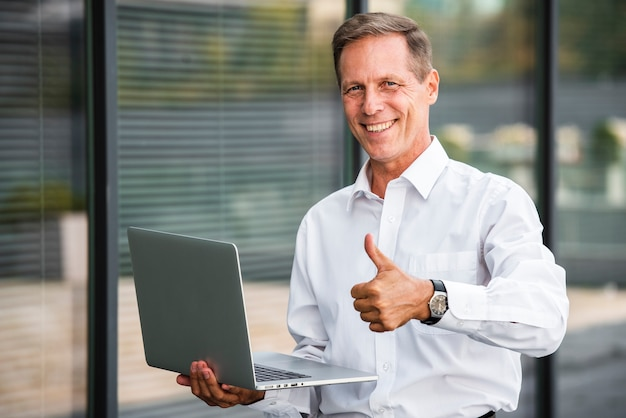 Businessman thumbs up holding laptop