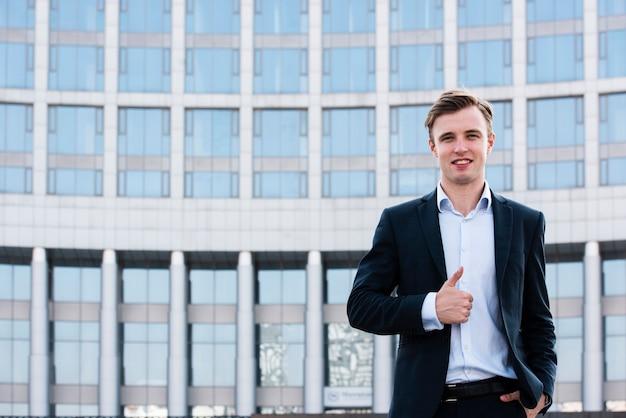 Businessman thumbs up looking at camera