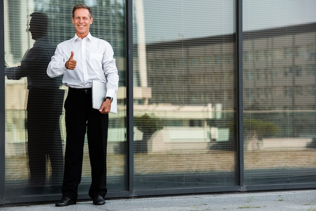 Businessman thumbs up near building