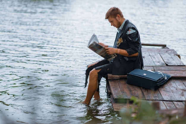 Businessman in torn suit reading newspaper on desert island.