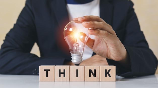 Касание бизнесмена электрическая лампочка на деревянных блоках куба со словом думает. творческий гений, новаторское знание, успешное. символ мышления творческая концепция.