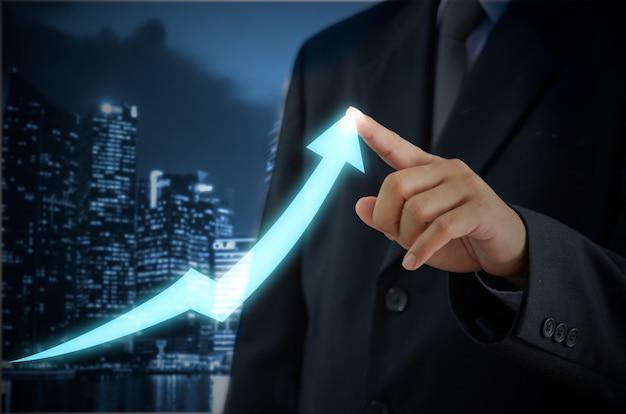 Бизнесмен касаясь стрелки на виртуальном экране. инвестиционный бизнес и экономическая концепция
