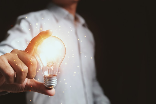 Businessman touching a bright light bulb. concept of ideas for presenting
