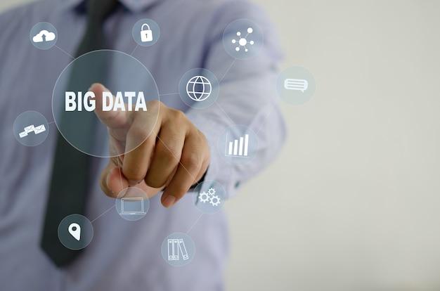 アイコンビッグデータ仮想画面に触れるビジネスマン。ビジネステクノロジーの概念、ビジネスマーケティング、投資、データ分析。コピースペース