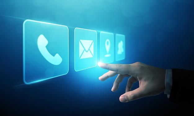Бизнесмен трогательно значок мобильного телефона, почты, телефона и адреса