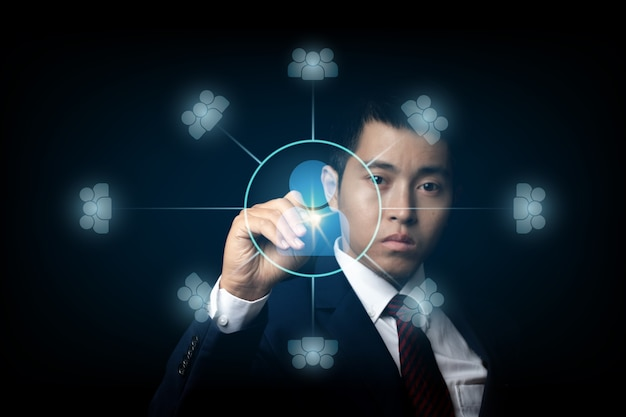Businessman touching screen, pushing on a icon connected together. cooperation, teamwork, network and community concept.