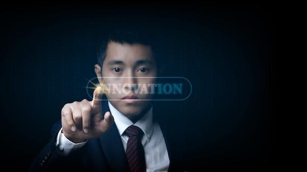 言葉の革新で仮想画面に触れるビジネスマン。イノベーションの概念。