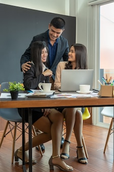 Businessman touching two asian businesswoman with formal suit in modern office when workin
