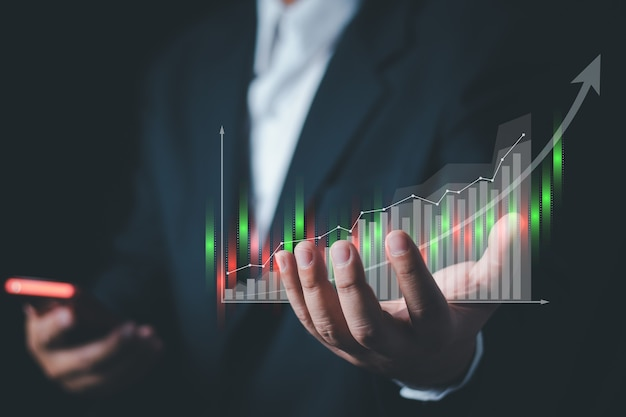 Businessman or trader is showing a growing virtual hologram stock. , planning and strategy, stock market, business growth, progress or success concept. , invest in trading.