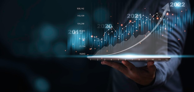 Businessman or trader showing glowing virtual technical investment graph chart for analysis stock market , banking financial and planing concept.