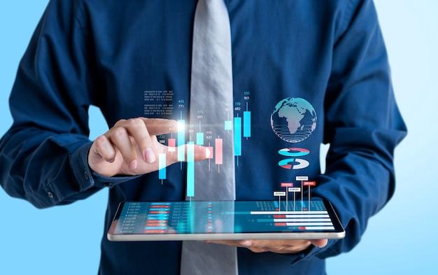 ビジネスマンは株式市場を取引し、タブレット画面に最新のグラフチャートを表示します