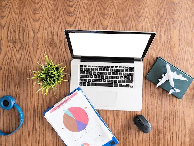 ビジネスマン旅行者のコンセプトイメージ。木製の机の上の平面図フラットレイ