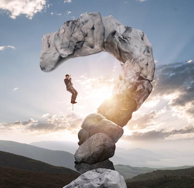 Бизнесмен пытается с трудом подняться на гору в форме вопросительного знака
