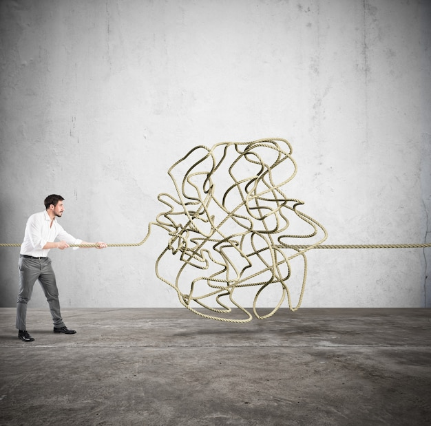 Businessman trying to solve the complicated tangle