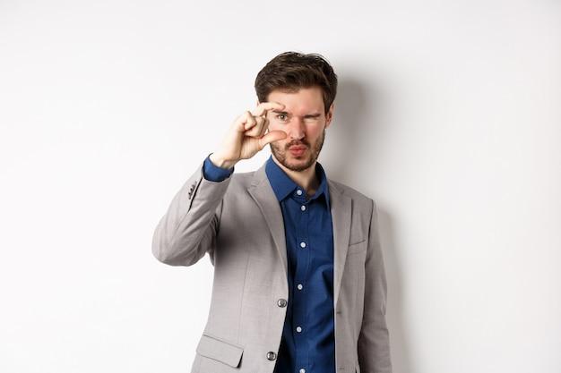 小さなものを見ようとしているビジネスマン、指で小さなもののサイズを示し、白い背景の上にスーツを着て立っています。