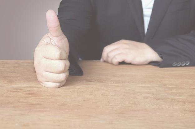 Businessman tump up hand in presentation on background.