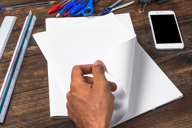 Businessman turning white blank paper with stationeries and smartphone on wooden table