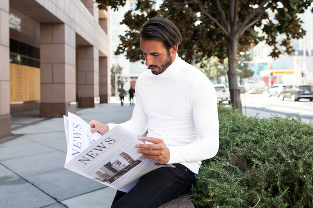 Businessman in turtleneck reading newspaper in the city