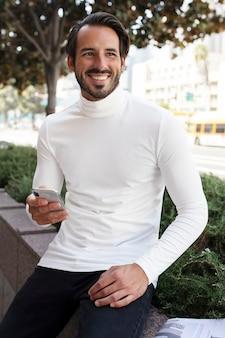Uomo d'affari in dolcevita seduto e sorridente in città