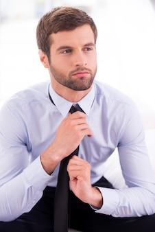 넥타이를 매는 사업가. 침대에 앉아있는 동안 넥타이를 매는 사려 깊은 젊은 사업가