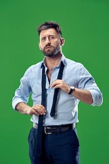 スタジオで彼のネクタイを結ぶビジネスマン。緑に孤立して立っている笑顔のビジネスマン