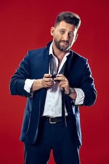 スタジオで彼のネクタイを結ぶビジネスマン。赤いスタジオの背景に孤立して立っている笑顔のビジネスマン。美しい男性の半分の長さの肖像画