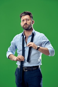 Uomo d'affari che lega la sua cravatta in studio. uomo d'affari sorridente in piedi isolato sul verde
