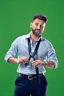 Businessman tying his tie at studio