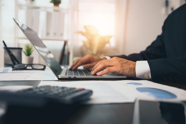 Бизнесмен печатает и работает на ноутбуке