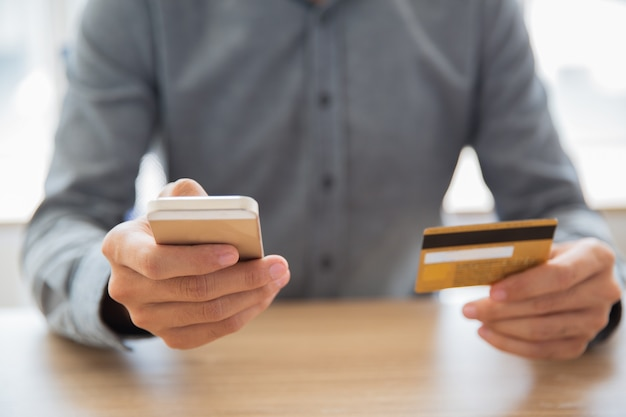携帯電話でカードデータを入力するビジネスマン