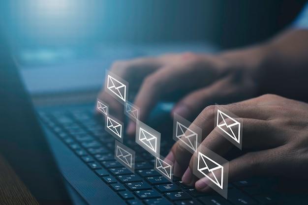 電子メールを送信するためにラップトップコンピューターを入力するビジネスマン、ビジネスの連絡先と通信の概念。