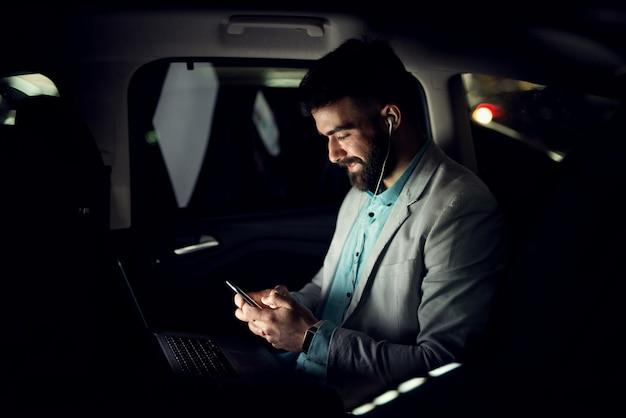 Businessman typing on mobile phone in the car.